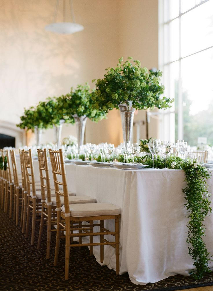 a lush greenery table runner and tall matching centerpieces make the tablescape look very fresh and very spring like