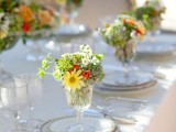 glasses with greenery and bright blooms will spruce up your wedding place settings in a cool way