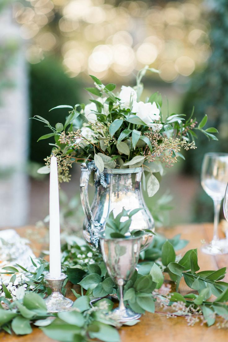 an elegant greenery and white bloom wedding centerpiece plus greenery on the table is a chic idea for a spring table
