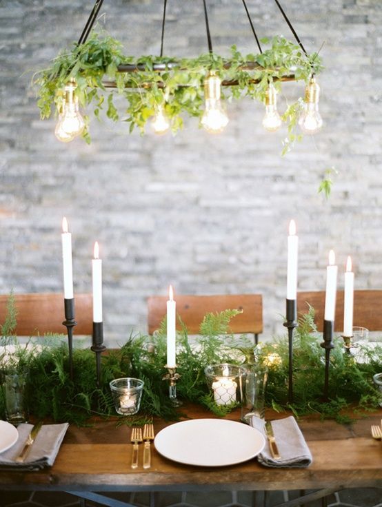 a fern table runner and a greenery chandelier with bulbs is a cool combo for a wedding tablescape