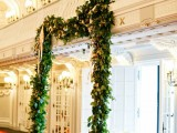 a creative wedding arch made of greenery and attached to the wall allows to have a ceremony without any problem everywhere