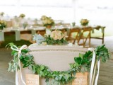 a sweetheart loveseat decorated with greenery and white ribbons is a cool idea to highlight your couple's seating