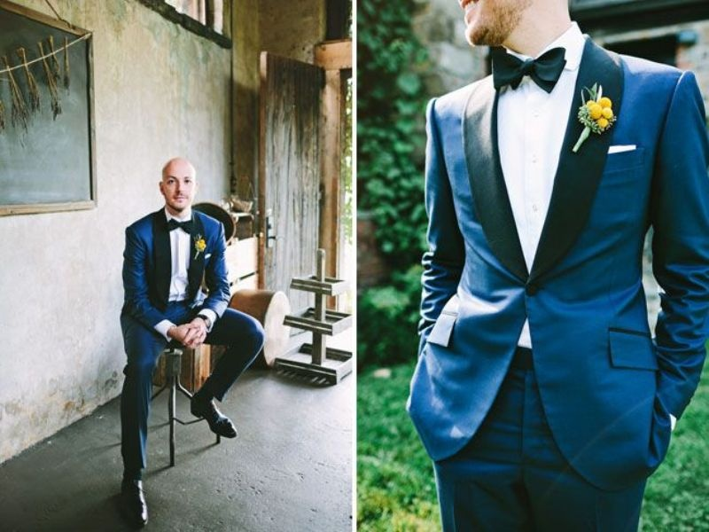 a navy tuxedo with black lapels, a black bow tie and a white shirt plus a colorful boutonniere