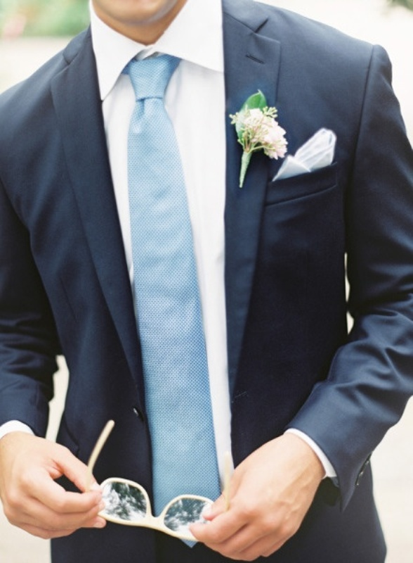 a navy suit, a white shirt, a light blue tie and a neutral boutonniere for a simple, elegant groom's look