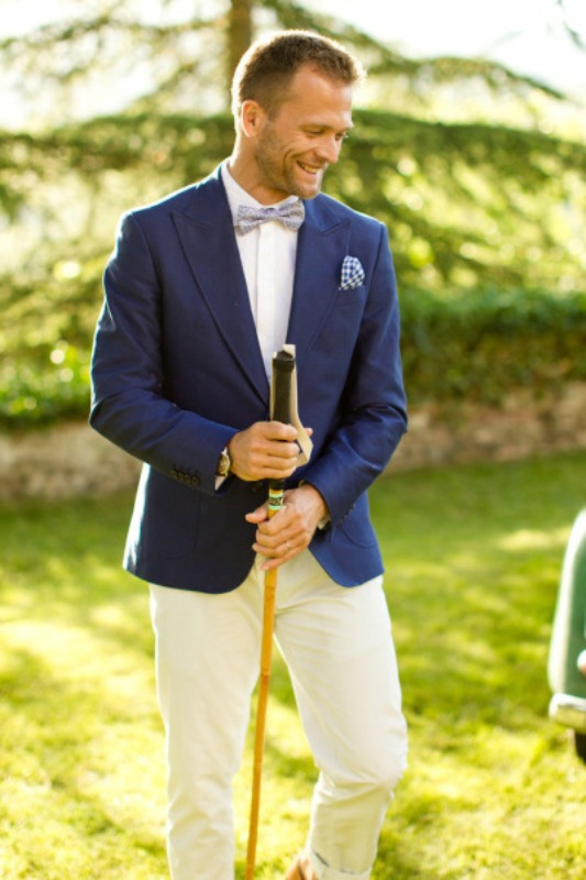 a navy blazer, a white shirt, a printed light blue bow tie and white pants create a contrasting look for your wedding