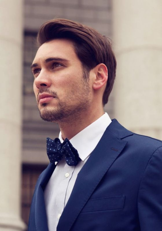 a navy suit, a white shirt and a navy printed bow tie create an elegant look with a contrasting touch