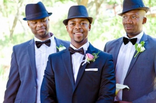 a navy suit, a white shirt, a black bow tie and a navy hat for a touch of retro