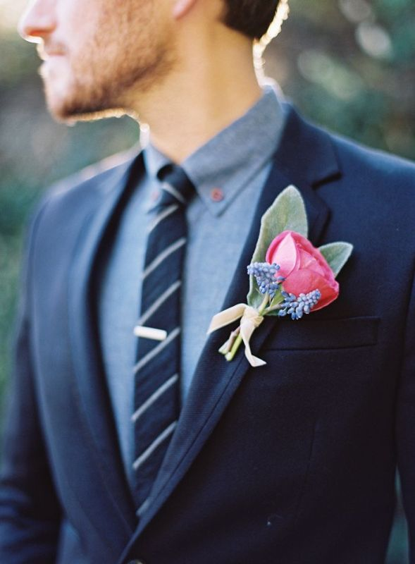 a navy woolen suit, a grey shirt, a striped navy and white tie and a bright floral boutonniere