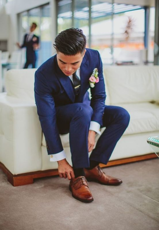 a navy suit, a white shirt, a black tie and brown shoes plus a pink boutonniere