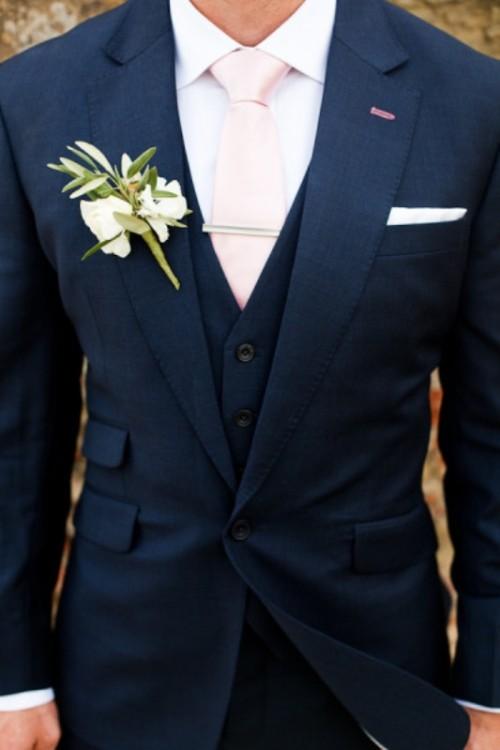 a navy three-piece suit, a white shirt, a blush tie plus a floral boutonniere