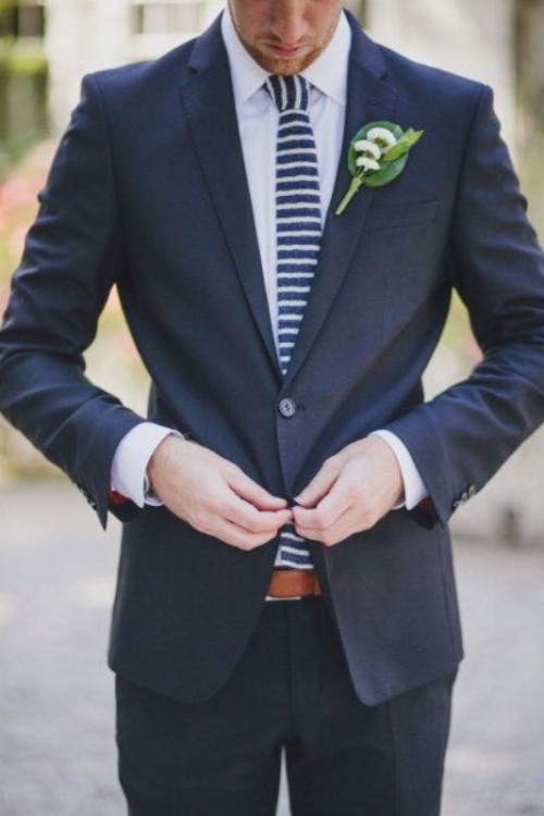 a navy suit, a white shirt are spruced up with a navy and white striped tie and a catchy boutonniere