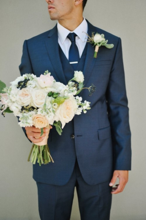 a navy three-piece suit, a white shirt and a navy tie plus a boutonniere for a bold and stylish look