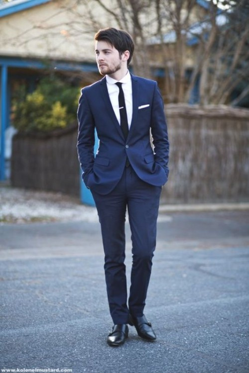 a navy suit, a white shirt, a black tie and black shoes for a modern to minimalist groom's outfit