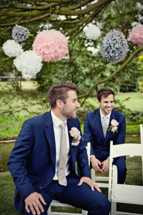 a navy suit, a white shirt, a grey tie and blush boutonnieres for a chic and elegant groom's look