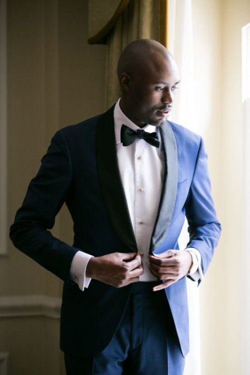 a super elegant navy tuxedo with black lapels, a black bow tie and a white shirt with pearly buttons