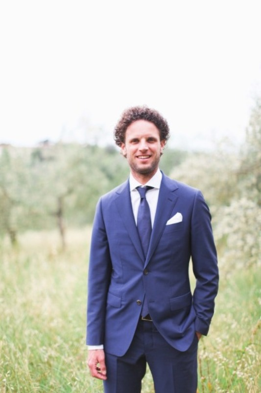 a navy suit, a navy tie and a white shirt for a simple and modern groom's look