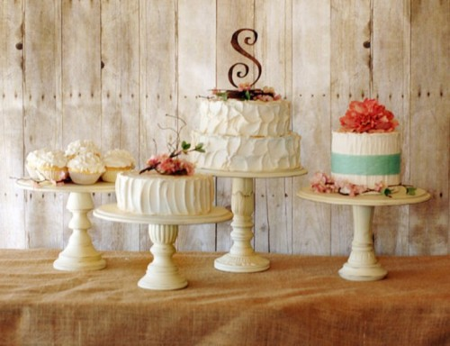 an assortment of rustic wedding cakes placed on various vintage rustic cake stands in white