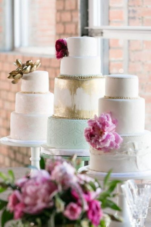 white cake stands and an assortment of various pastel and metallic wedding cakes with pink blooms
