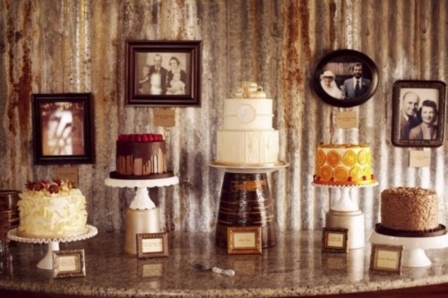 all different wedding cakes placed on white stands and a large metal one to highlight the main cake