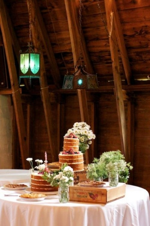 a rustic sweet table a crate and a wooden stand plus some white blooms and greenery is a cool rustic idea