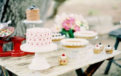 simple glass and white stands for an assortment of wedding cakes on a shabby chic table