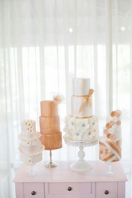 white and sheer glass cake stands with an assortment of peachy and white wedding cakes with ribbons