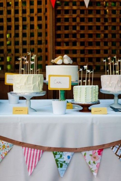 blue, turquoise and wooden cake stands and an assortment of pastel wedding cakes with cute toppers