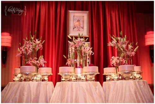 an assortment of pink wedding cakes that are placed on metallic stands and lush floral centerpieces