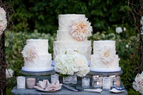 sheer glass cake stands, lace wrapped candleholders and white blooms make the cake table feel rustic