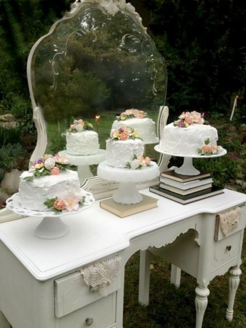 a vintage dresser with elegant vintage cake stands placed on books is ideal for a vintage wedding