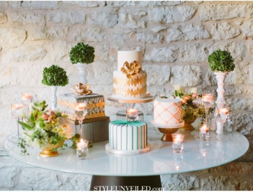 an assortment of wood and metal stands for various wedding cakes and topiaries that settle down one style at this eclectic sweets table