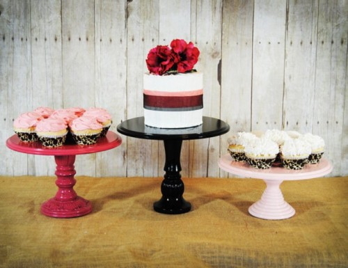 wooden stands of pink for cupcakes and a black cake stand make up a rustic and a cool sweets table