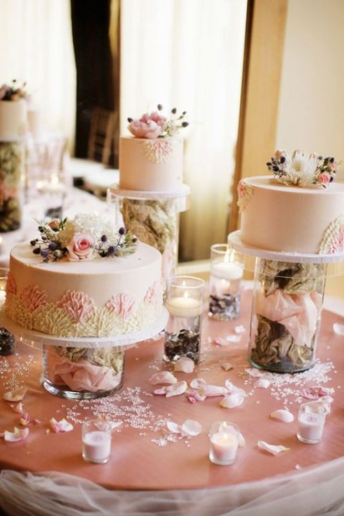 creative cake stands - glasses filled with dried flower petals finish off the look of the cakes with fresh blooms and greenery
