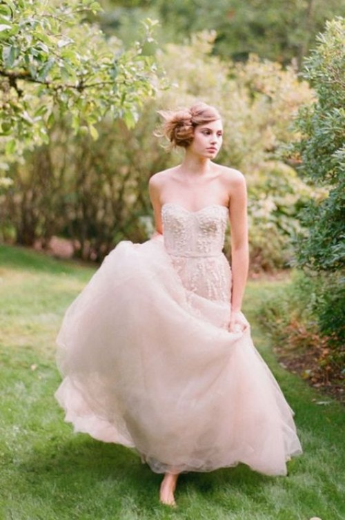 a tender blush strapless wedding dress with a layered skirt and an embellished bodice for a dreamy princess-like look