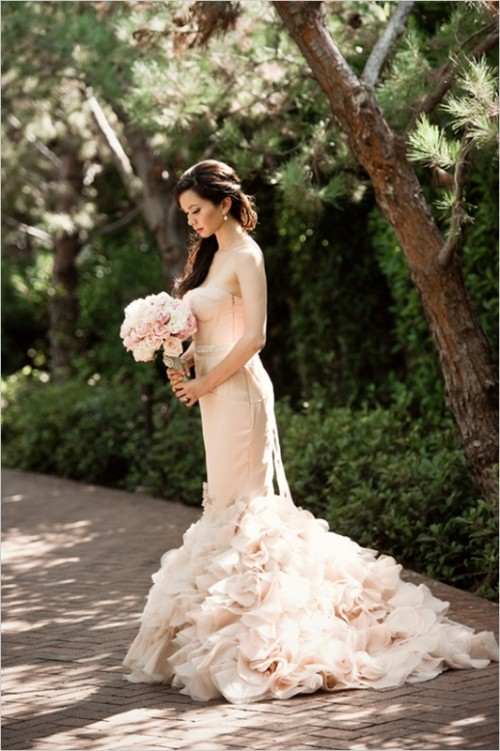 a gorgeous blush strapless mermaid wedding dress with a pretty ruffle tail and an embellished sash for a romantic bride