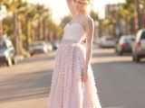 a strapless blush wedding dress with a draped bodice and a ruffle midi skirt and an embllished sash