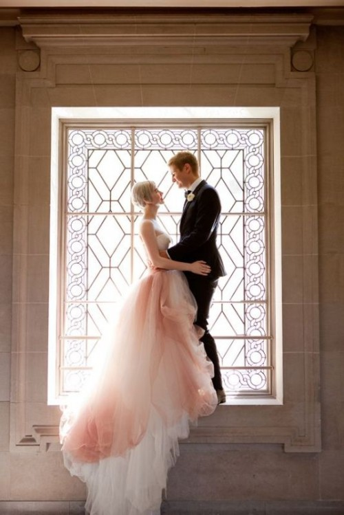 an ombre pink and white wedding ballgown with a strapless bodice and a layered skirt with a train