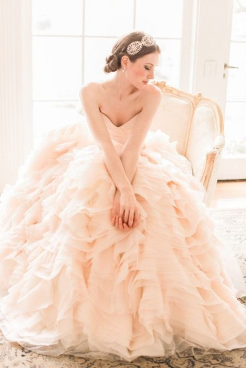 a strapless blush wedding ballgown with a draped bodice, a layered ruffled skirt for a classic and chic look