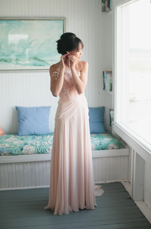 a whimsy blush wedding dress with a draped bodice and feathers on it and a pleated skirt