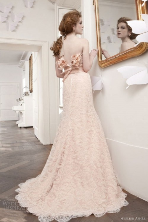a beautiful blush lace A-line wedding dress with blush fabric blooms decorating the open back