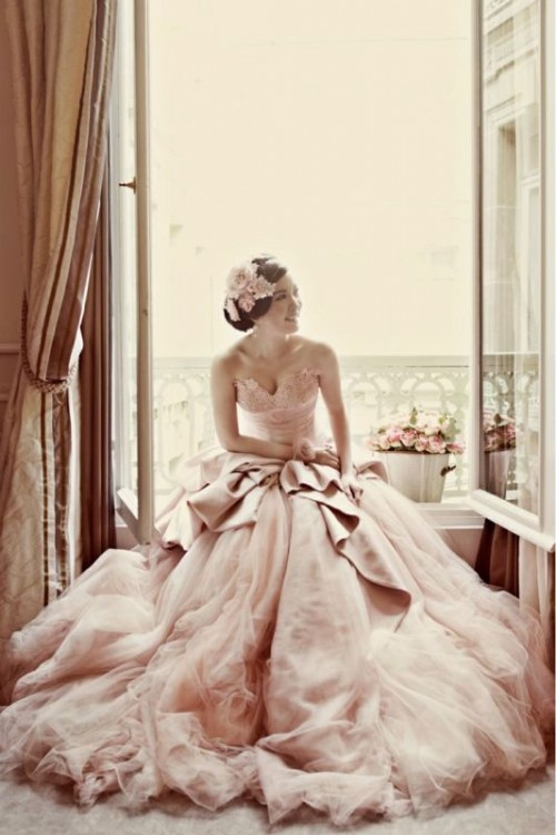 a blush wedding ballgown with a lace bodice and a layered skirt with a train for a modern princess