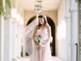 a blush lace A-line wedding dress with a tulle skirt and a lace bodice plus a matching veil for a modern romantic bridal look