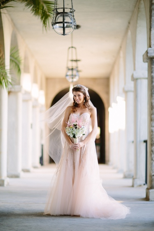 a blush lace A line wedding dress with a tulle skirt and a lace bodice plus a matching veil for a modern romantic bridal look