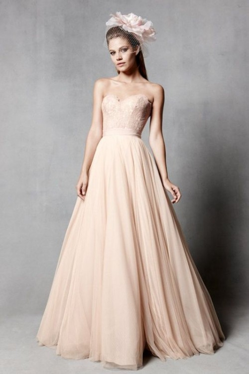 a blush strapless A-line wedding dress with a lace bodice and a plain skirt is a pastel take on classics