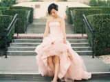 a strapless A-line high low wedding dress with a train and a draped bodice and skirt