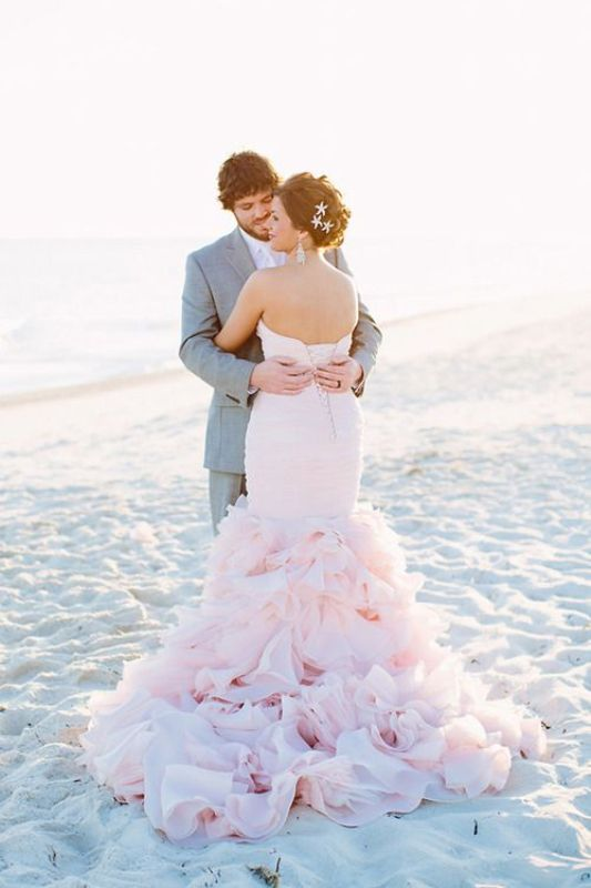 a blush strapless wedding dress with a draped bodice and a pretty ruffle tail for a sweet beach bride