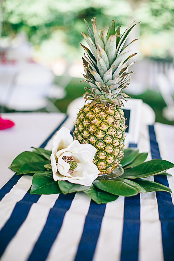 a pineapple with leaves and neutral blooms form a great and simple wedding centerpiece for a tropical wedding