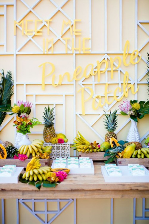 a fruit table with lots of bananas, papayas, pineapples, leaves and bright blooms is great instead of a usual dessert table