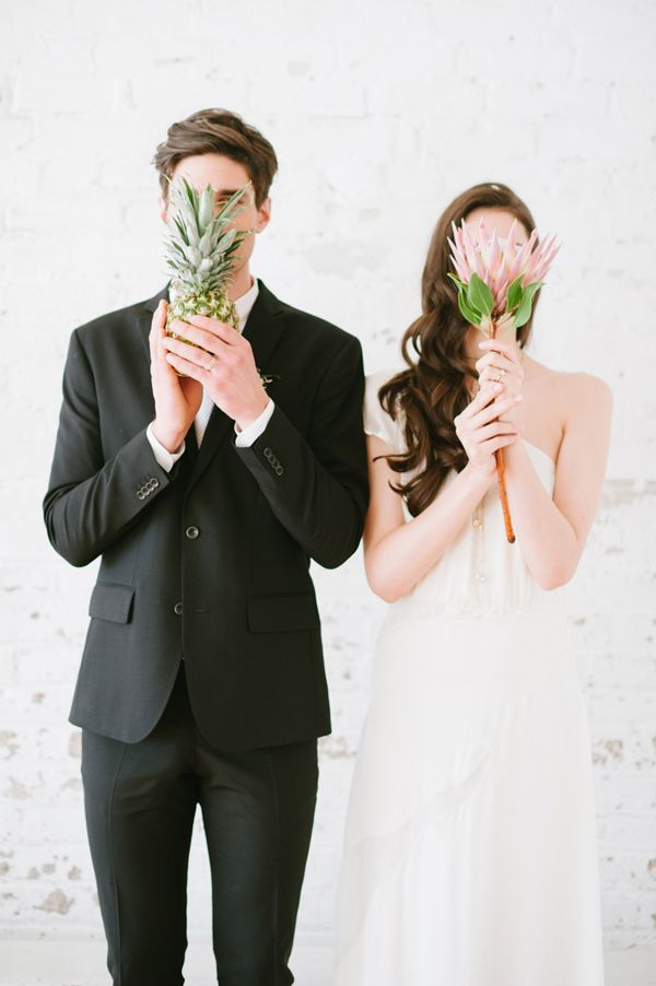 a bride holding a large bloom and a groom holding a pineapple remind that their wedding is a tropical one