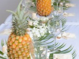 a tropical wedding tablescape with leaves, white tropical blooms and pineapples plus candles is lovely and chic